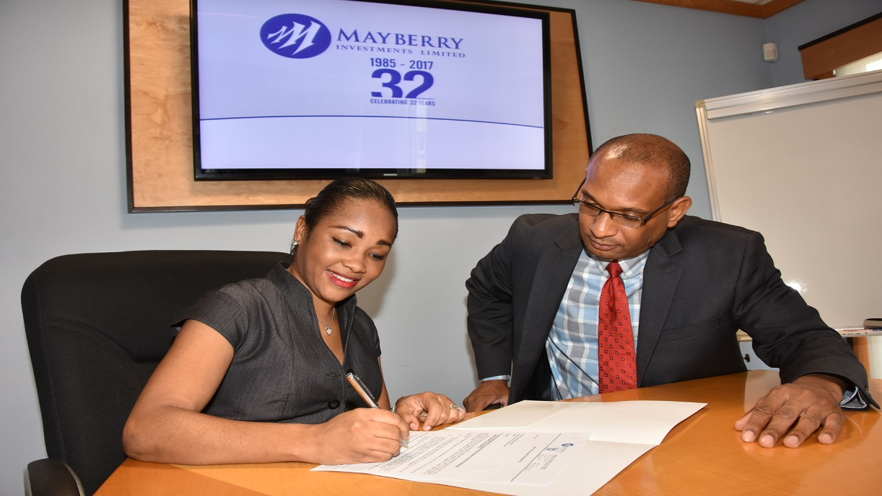 "Mayberry's Senior VP of Investment Banking, Tania Waldron-Gooden, signs ""Lockup Agreement"" with Scotia Group Jamaica Limited. Looking on is CEO of Scotia Investments, Lissant Mitchell."