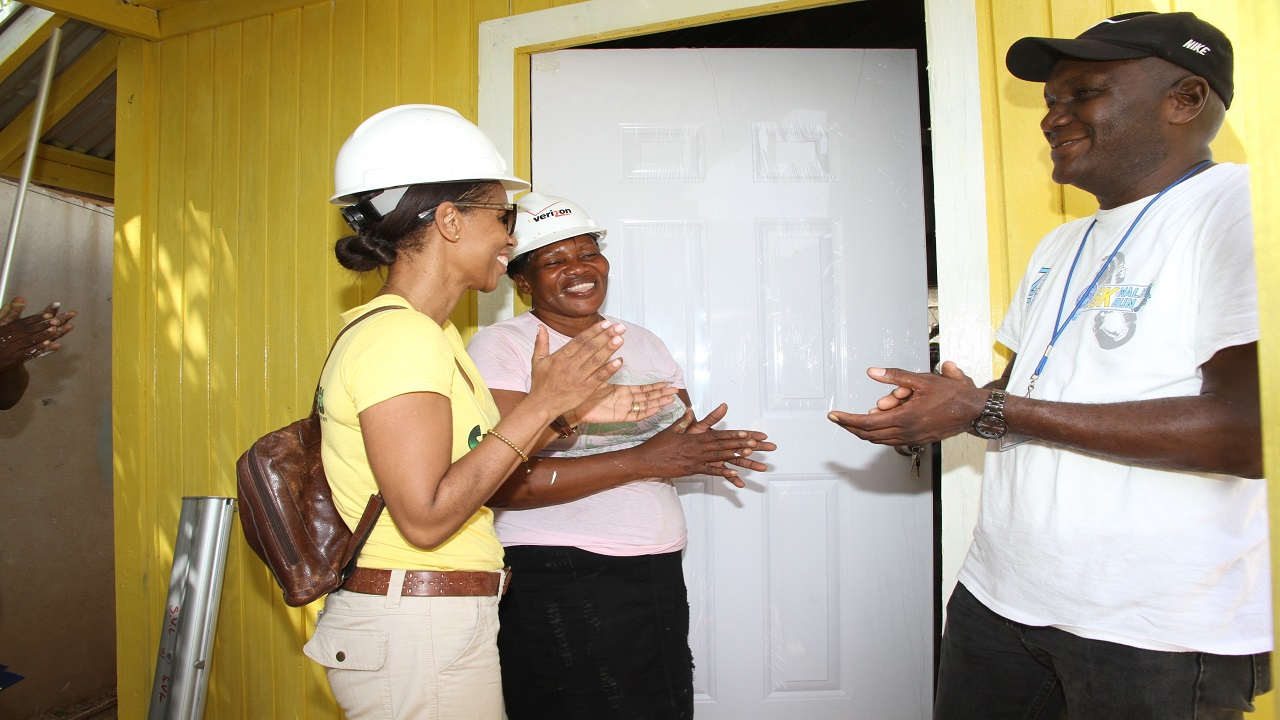 Food for the Poor house beneficiary, Beverly Foote opens the door of her new two bedroom house for the first time in Irish Pen, Spanish Town, St Catherine on Thursday, July 20. Sharing in the moment are Supreme Ventures AVP, Group Corporate Communications, Simone Clarke-Cooper (left) and FFP Senior Field Officer, Lorenzo Stanton.