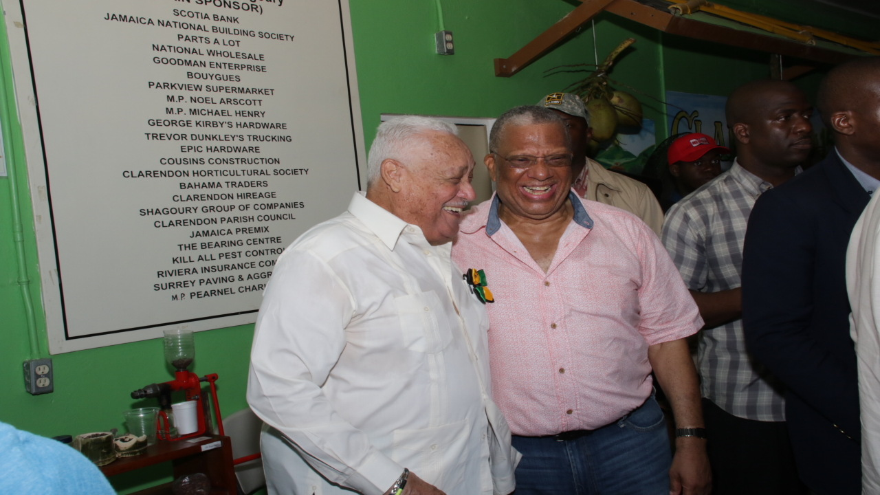 Opposition Leader Dr Peter Phillips (right) shares a laugh with Transport Minister Mike Henry at Denbigh. (PHOTO: Llewellyn Wynter)