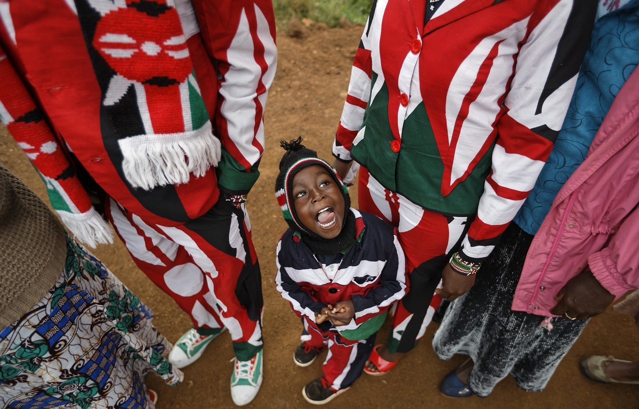 Joseph Njoroge Kimani, 3, stands with his father James Kimani Njoroge, left, and mother Esther Wanjiru Njoroge, right, all wearing suits made in the colors of the Kenyan flag, as they queue to cast their votes in Gatundu, north of Nairobi, in Kenya Tuesday, Aug. 8, 2017.