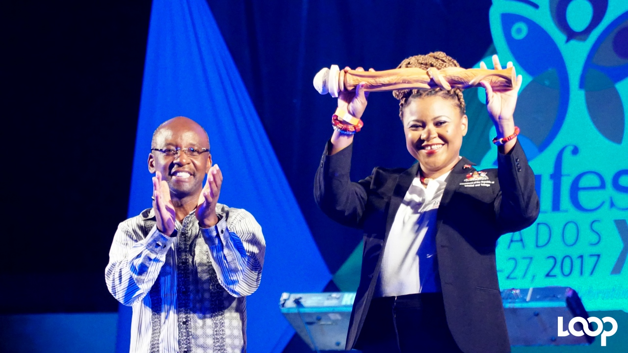 Trinidad & Tobago's Minister of Community Development, Culture and the Arts, Dr. Nyan Gadsby-Dolly holds the Carifesta baton high after receiving it from Barbados' Culture Minister Stephen Lashley at the Closing Ceremony of CARIFESTA XIII.
