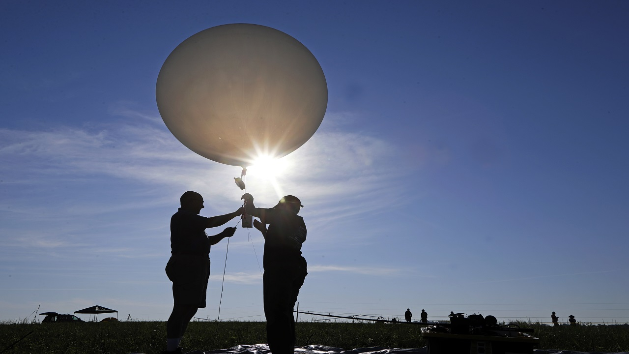 Mike Newchurch, left, professor of atmospheric chemistry at the University of Alabama in Huntsville, and graduate student Paula Tucker prepare a weather balloon before releasing it to perform research during the solar eclipse Monday. (PHOTOS: AP)