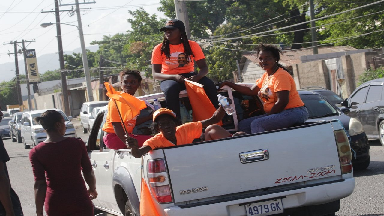 Comrades travel in the back of a van last month to participate in an internal election to select the PNP's representative for South West St Andrew.