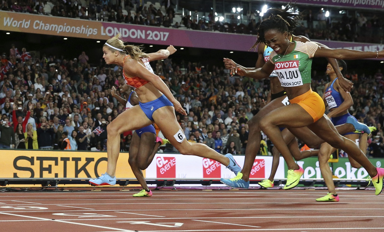 Netherlands' Dafne Schippers, left, crosses the line to win the gold in the women's 200m final during the World Athletics Championships in London Friday, Aug. 11, 2017. Right is Ivory Coast's Marie-Josee Ta Lou.