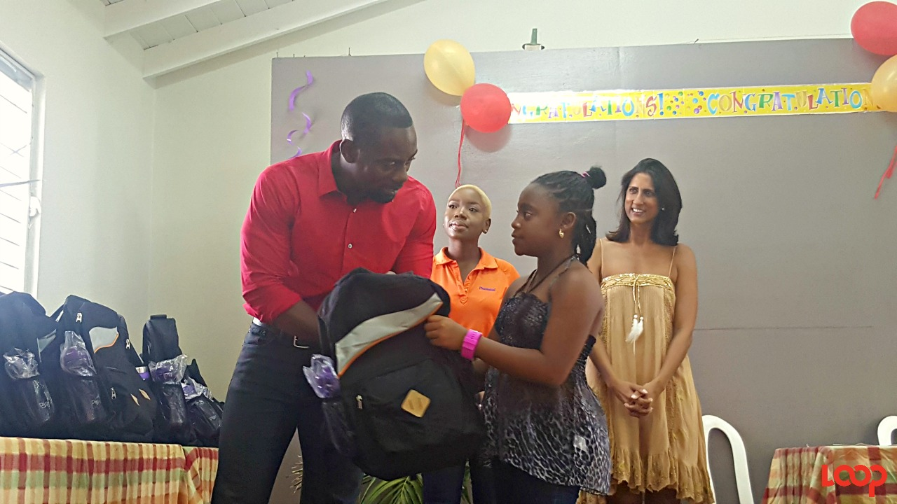 (Left) BLP St. Michael South Candidate Kirk Humphrey presenting the supplies and school bag to Latia McClean-John, who attended Bay Primary and is off to Springer Memorial Secondary School in Spetember.