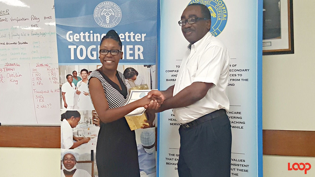 Intern of the Year 2016-2017 Dr. Simone Evelyn receiving her gifts from the Director of Medical Services at the QEH, Dr. Anthony Harris.