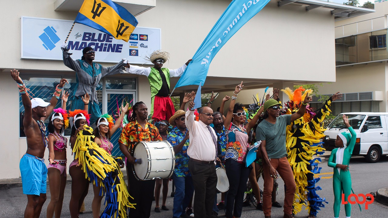 (center L-R) The CEO of the NCF Cranston Browne, General Manager Retail Banking at Republic Bank Sharon Zephirin and Grand Kadooment Producer Adisa 'Aja' Andwele flanked by dancers, tumblers and stilt walkers.