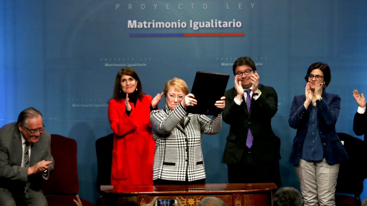 Chile's President Michelle Bachelet holds up a portfolio containing her signed proposal for a same-sex marriage bill at La Moneda presidential palace in Santiago, Chile, Monday, Aug. 28, 2017. (AP Photo)