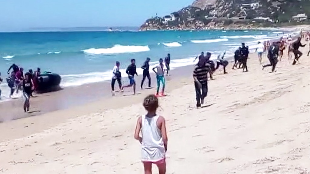 Beachgoers watch migrant boat land on Spanish shore