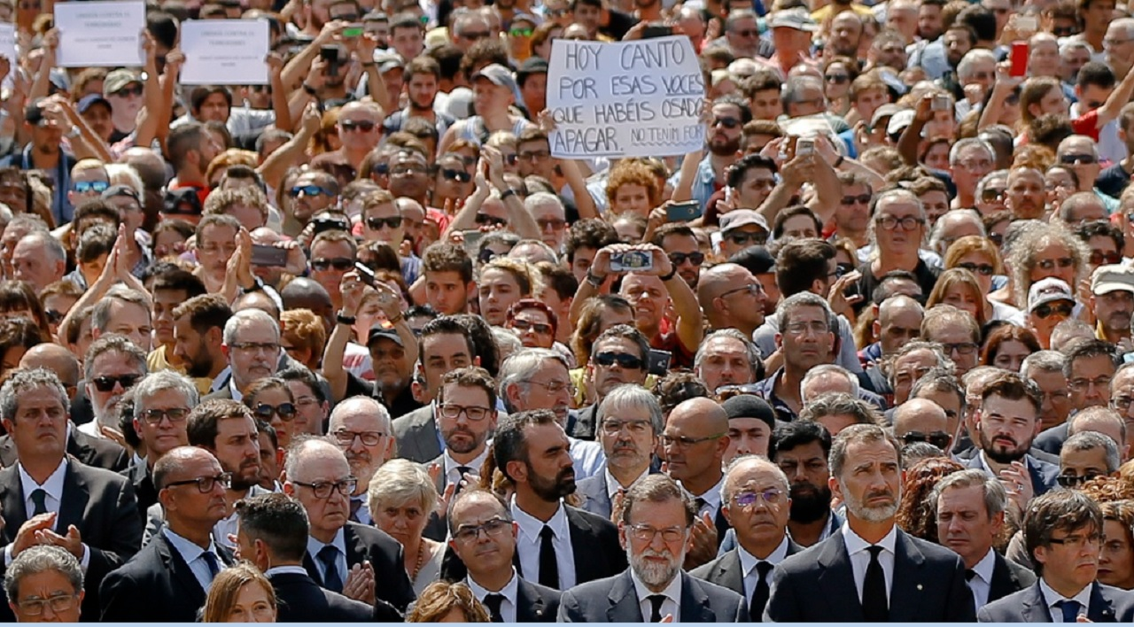 "A woman, center, holds a banner that reads ""Today I sing for voices you dared to silence - We are not afraid"" as people observe a minute of silence in memory of the terrorist attacks victims in Las Ramblas, Barcelona, Spain, Friday, Aug. 18, 2017, joined by King Felipe of Spain, second from right, Prime Minister Mariano Rajoy, third from right, and and Catalonia regional President Carles Puigdemont, right, on the front row."