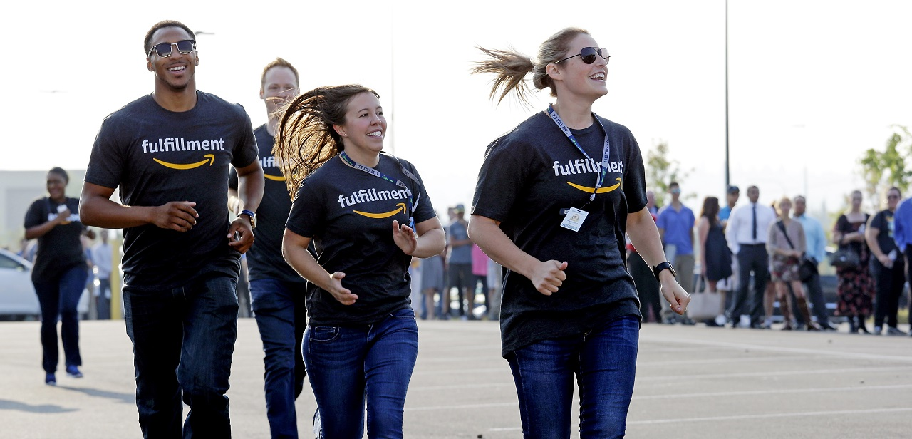 Amazon workers run past a line of applicants waiting to enter a job fair after greeting them with high-fives, Wednesday, Aug. 2, 2017, at an Amazon fulfillment center, in Kent, Wash. Amazon plans to make thousands of job offers on the spot at nearly a dozen U.S. warehouses during the recruiting event.