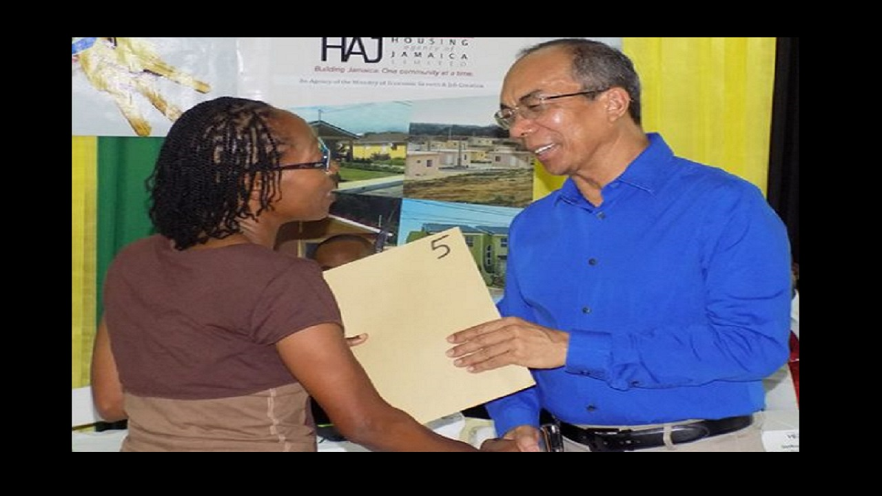 Minister without Portfolio in the Ministry of Economic Growth and Job Creation, Hon. Dr. Horace Chang (right), presents Norwood resident, Curdillio Evans, with her land title. Photo via JIS.