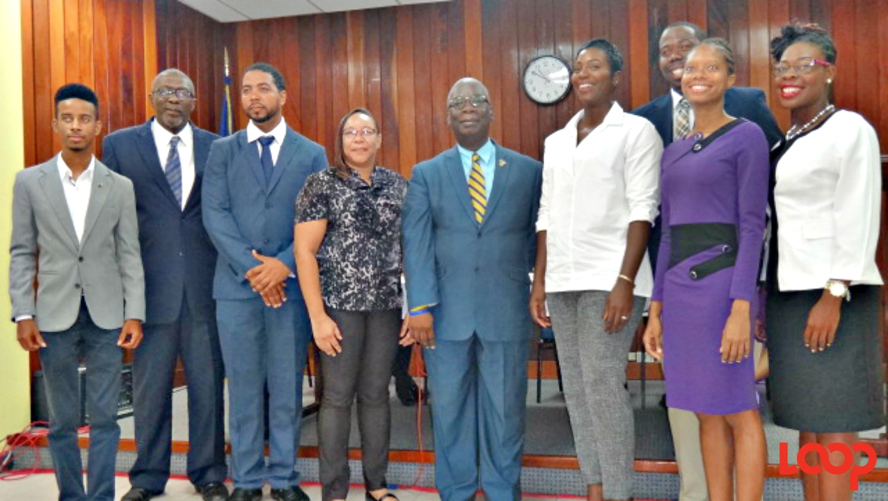 Education Minister Ronald Jones (centre) and Parliamentary Secretary Senator Harcourt Husbands (second left) with this year's cohort of National Development Scholars and Commonwealth Scholar, Cherisse Francis (right).