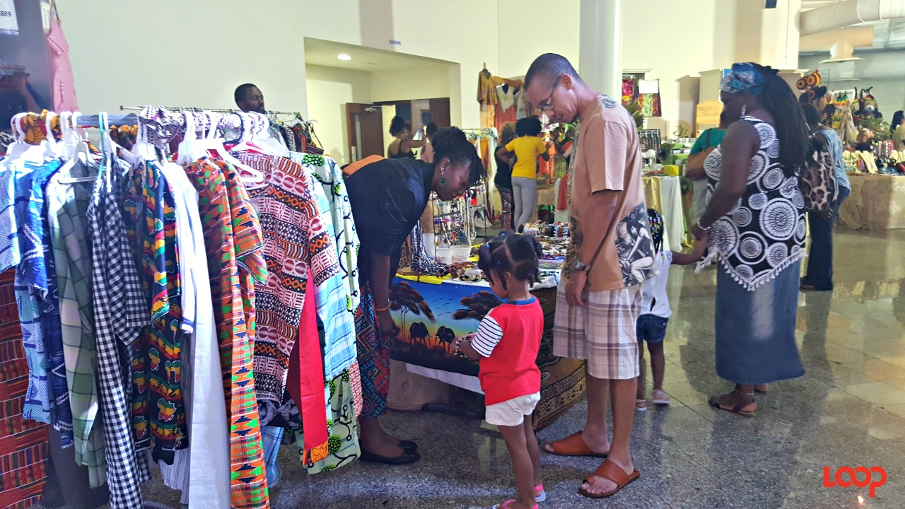 Some parents used the opportunity to take their children to learn about the cultures of the Caribbean at the CARIFESTA XIII Grand Market. This dad bought his daughter a bracelet.