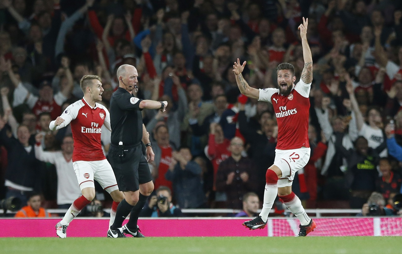 Arsenal's Olivier Giroud  celebrates as referee Mike Dean, centre, says the ball has crossed the line for a goal during their English Premier League football match against Leicester City at the Emirates stadium in London on Friday.  Arsenal won the match 4-3.