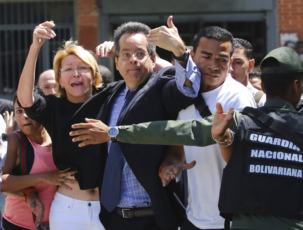 Venezuelan General Prosecutor Luisa Ortega Diaz, left, is surrounded by loyal employees of the General Prosecutor's office, as she was barred from entering by security forces, outside of the General Prosecutor headquarters in Caracas, Venezuela, Saturday, Aug. 5, 2017. (AP Photo/Wil Riera)