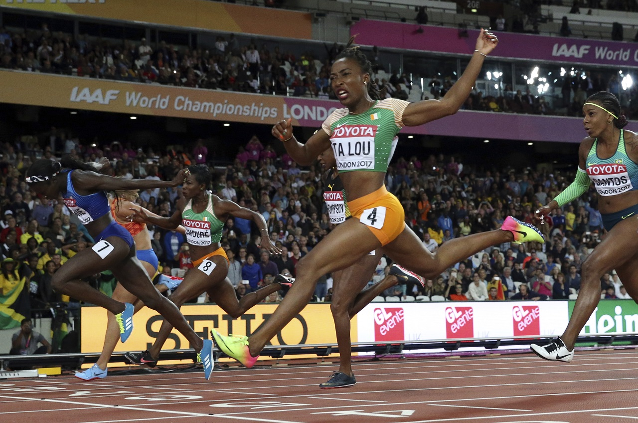 United States' Tori Bowie, left, crosses the line to win the gold in the women's 100-meter final during the World Athletics Championships in London Sunday, Aug. 6, 2017.