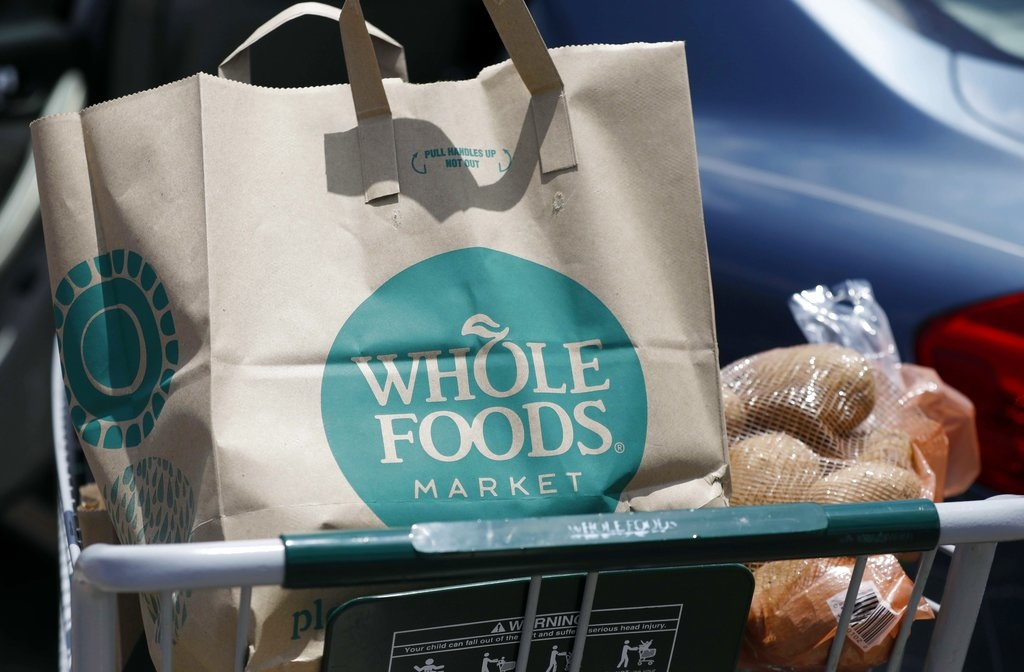 In this Friday, June 16, 2017, file photo, groceries from Whole Foods Market sit in a cart before being loaded into a car, outside a store in Jackson, Miss. On Wednesday, Aug. 23, 2017, Whole Foods shareholders will be voting on whether to approve Amazon's $13.7 billion takeover bid of the organic grocer. (AP Photo/Rogelio V. Solis, File)