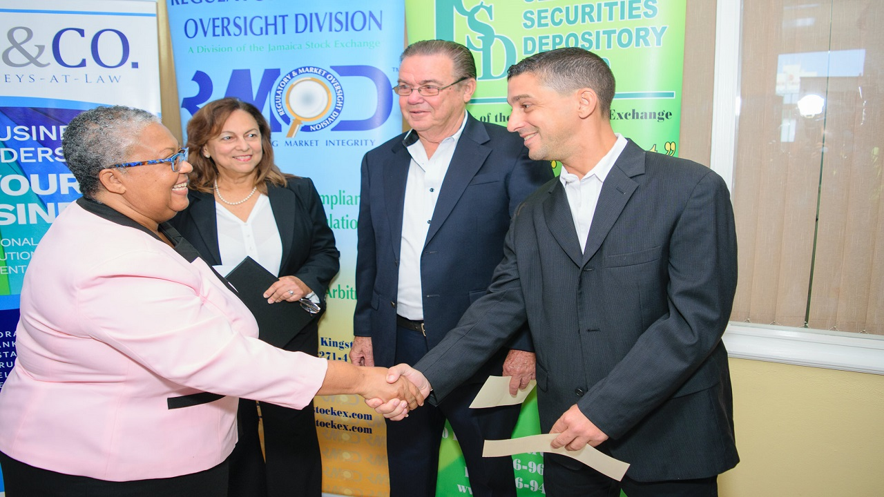 Marlene Street Forrest, Managing Director of the Jamaica Stock Exchange, greets Allan McDaniel,  Deputy Managing Director and Director of Warehouse and Logistics of SOS Limited. Looking on are parents and fellow directors, Marjorie McDaniel, Director, Chief Administrative Officer and Company Secretary and David McDaniel, Chairman and Managing Director of SOS Limited.