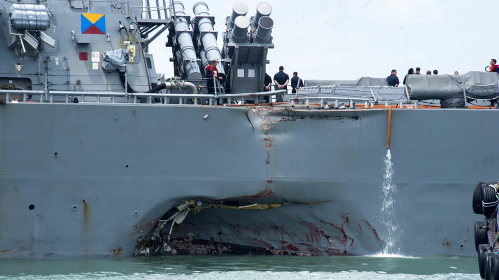 The damaged port aft hull of USS John S. McCain, is seen while docked at Singapore's Changi naval base on Tuesday, Aug. 22, 2017 in Singapore. The focus of the search for 10 U.S. sailors missing after a collision between the USS John S. McCain and an oil tanker in Southeast Asian waters shifted Tuesday to the damaged destroyer's flooded compartments. (AP Photo/Wong Maye-E)