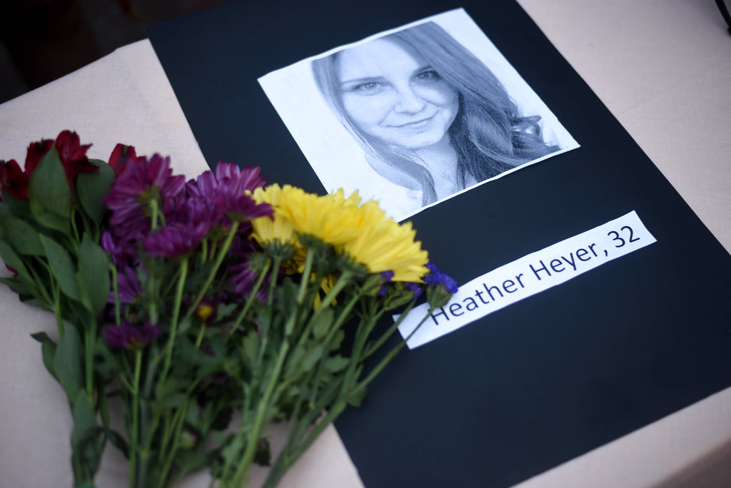 A portrait of Heather Heyer, who was killed when a vehicle drove through counter protestors in Charlottesville, Va., lies on a table with flowers during a vigil on the campus of the University of Southern Mississippi in Hattiesburg, Miss., Monday, Aug 14, 2017. The rally was held in response to a white nationalist rally held in Charlottesville, Va., over the weekend. (Courtland Wells/The Vicksburg Post via AP)