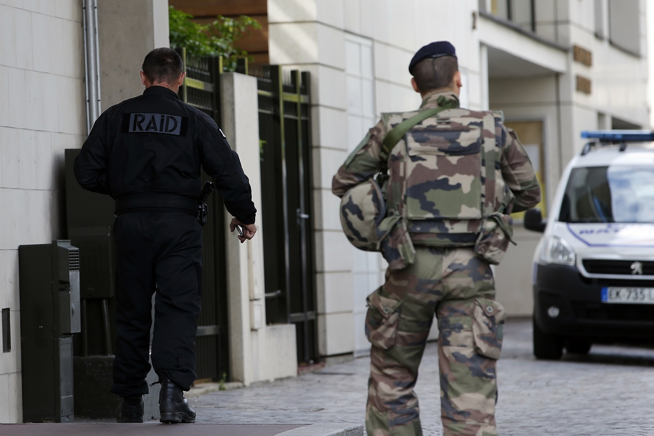 French soldiers walk near the scene where French soldiers were hit and injured by a vehicle in the western Paris suburb of Levallois-Perret near Paris, France, Wednesday, Aug. 9, 2017.