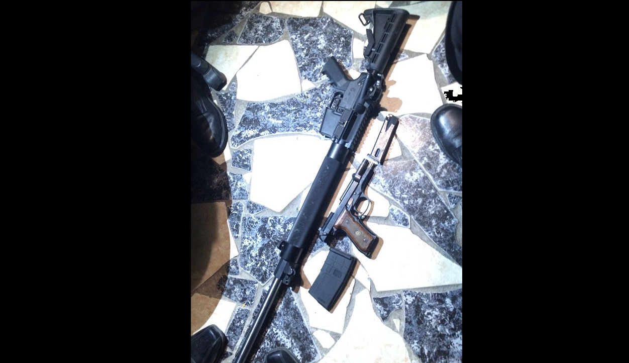 The M16 rifle and hand gun that were reportedly recovered from the scene.