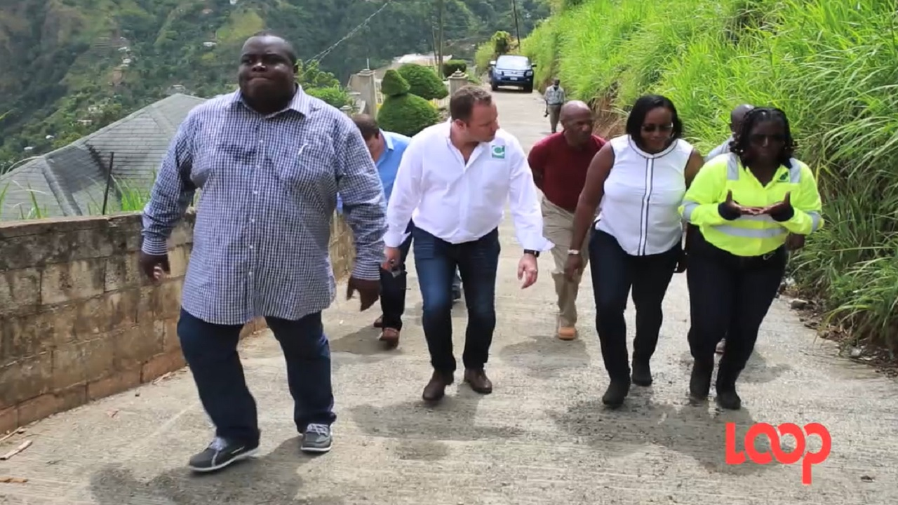 Carib Cement general manager Peter Donkersloot (third left) and East Rural St Andrew Member of Parliament Juliet Holness (second right) are pictured among a group of persons walking along the new concrete roadway on Friday.