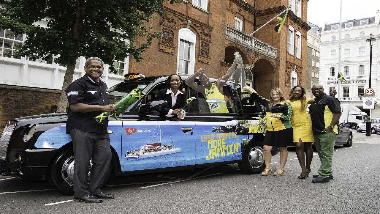 Jamaica Tourist Board staff pose with one of the Jamaica wrapped taxis that is showcasing the island across the city of London. From left are: Torrance Lewis, District Sales Manager;  Antoinette Charles, Personal Assistant to Regional Director UK/Northern Europe; Elizabeth Fox, Regional Director UK/Northern Europe; Yollette Scarlett Accounts/Sales Support Executive and Donovan Donaldson, Business Development Officer.