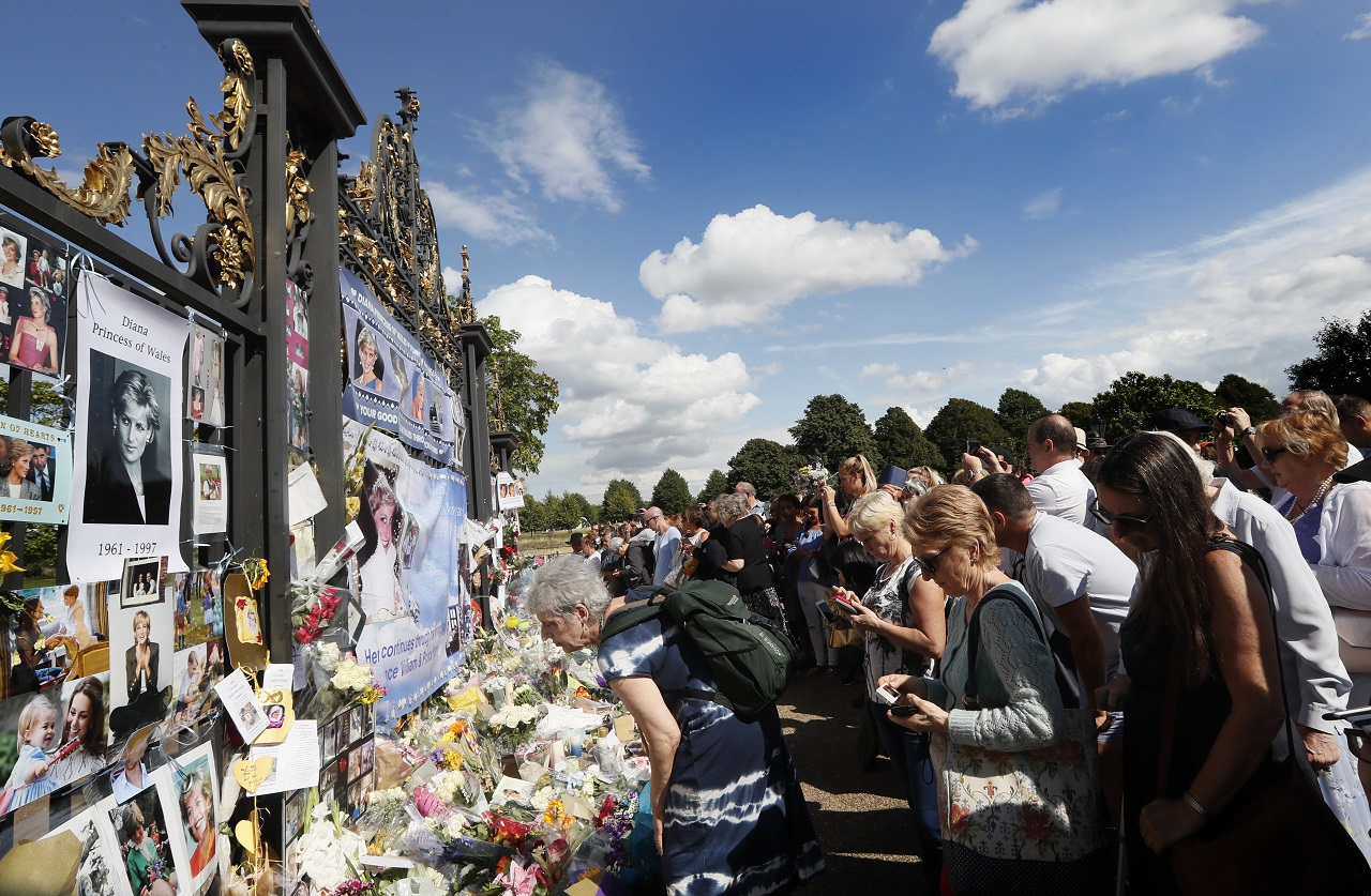 People crowd around the gates of Kensington Palace in London to pay tribute to the late Diana, Princess of Wales, Thursday, Aug. 31, 2017. Tributes at the gates are to mark the 20th anniversary of Diana's death, in a car crash in Paris on Aug. 31, 1997.