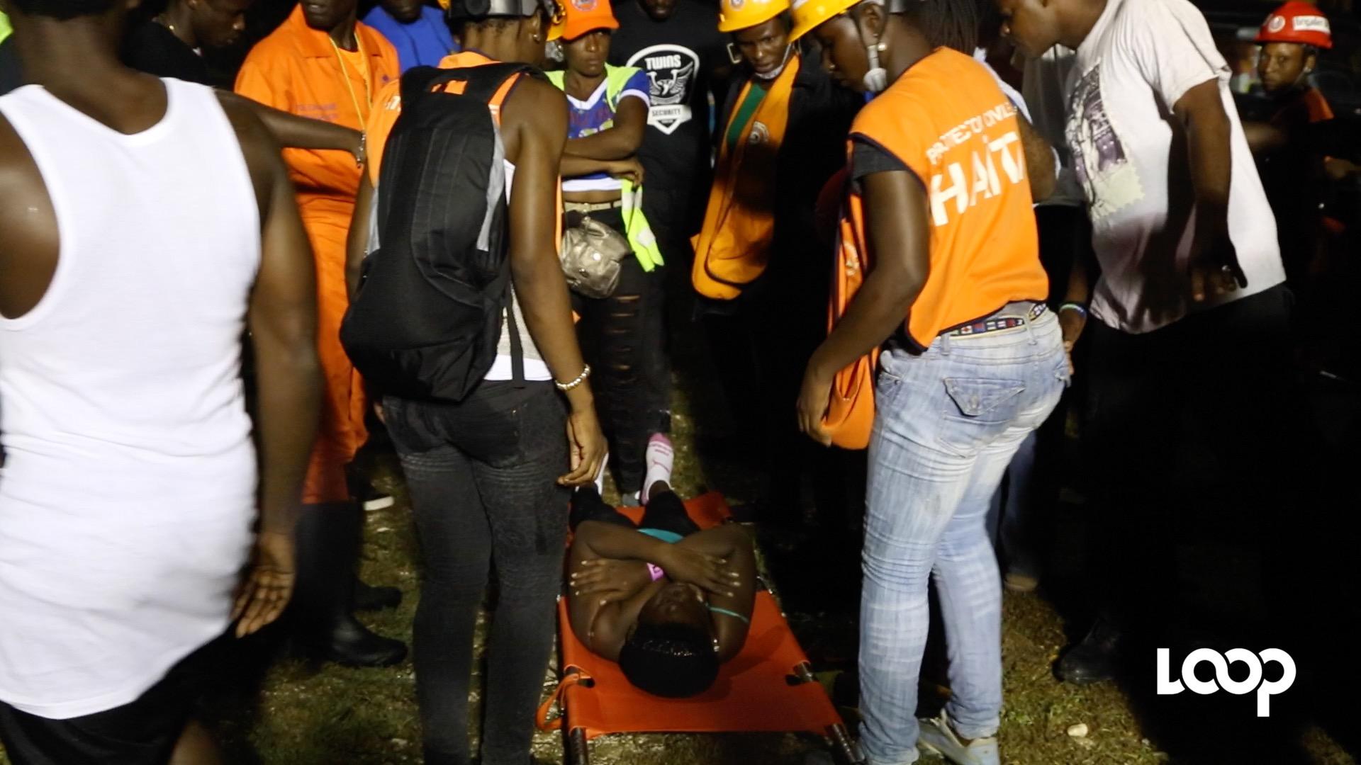 La jeune femme allongée au sol, les mains en croix sur le buste reçoit les premiers soins du service ambulancier du festival/Photo: Estailove St-Val