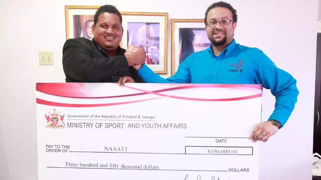 The Honourable Darryl Smith, Minister of Sport and Youth Affairs, presents NAAATT's Chief Administrative Officer, Mr. Kabir Hosein with cheque for $350,000 (Ministry of Sport and Youth Affairs)