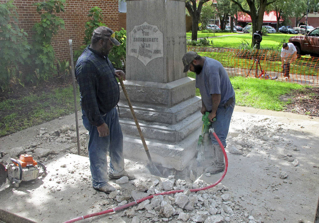 Workers begin removing a Confederate statue in Gainesville, Fla., Monday, Aug. 14, 2017. The statue is being returned to the local chapter of the United Daughters of the Confederacy, which erected the bronze statue in 1904. County officials said they did not know where the statue would be going. (AP Photo/Jason Dearen)