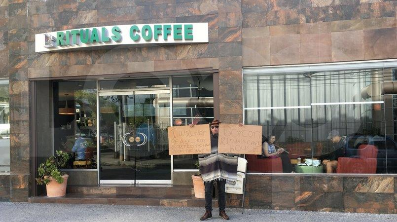 In this June 27, 2017 photo, Ian Smart holds up placards calling for a boycott of Rituals outside of the Maraval Road branch of the business.