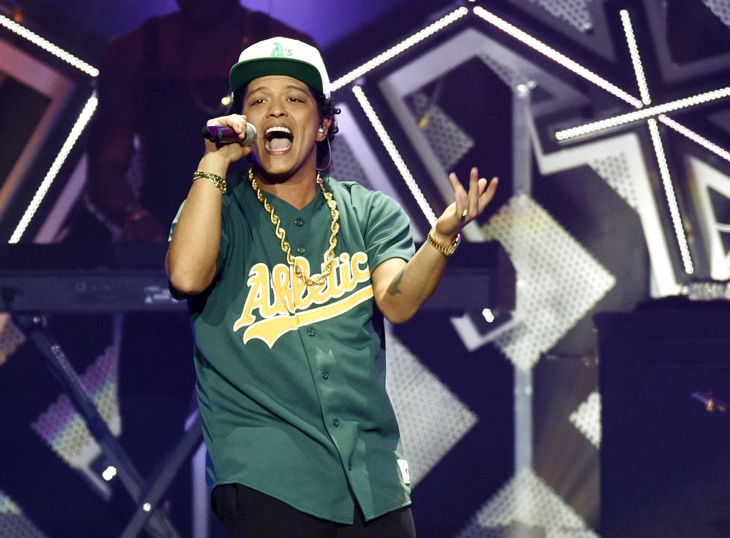 In this Dec. 2, 2016 file photo, Bruno Mars performs at the 2016 Jingle Ball at Staples Center in Los Angeles. Mars is donating $1 million from his Michigan concert to aid those affected by the Flint water crisis. (Photo by Chris Pizzello/Invision/AP, File)