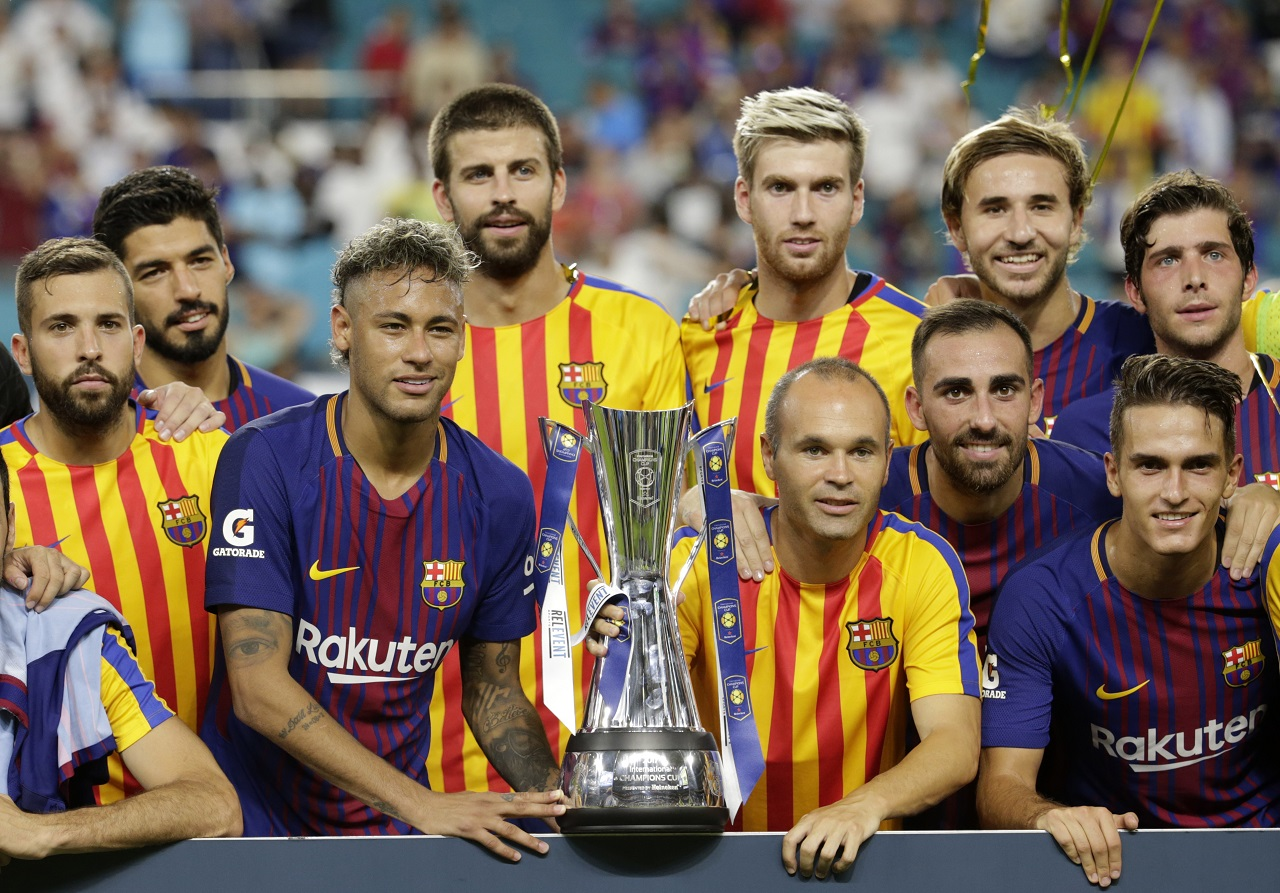 Barcelona's Neymar, second from left front, and teammates pose with the trophy after defeating Real Madrid in an International Champions Cup soccer match, Saturday, July 29, 2017, in Miami Gardens, Fla.