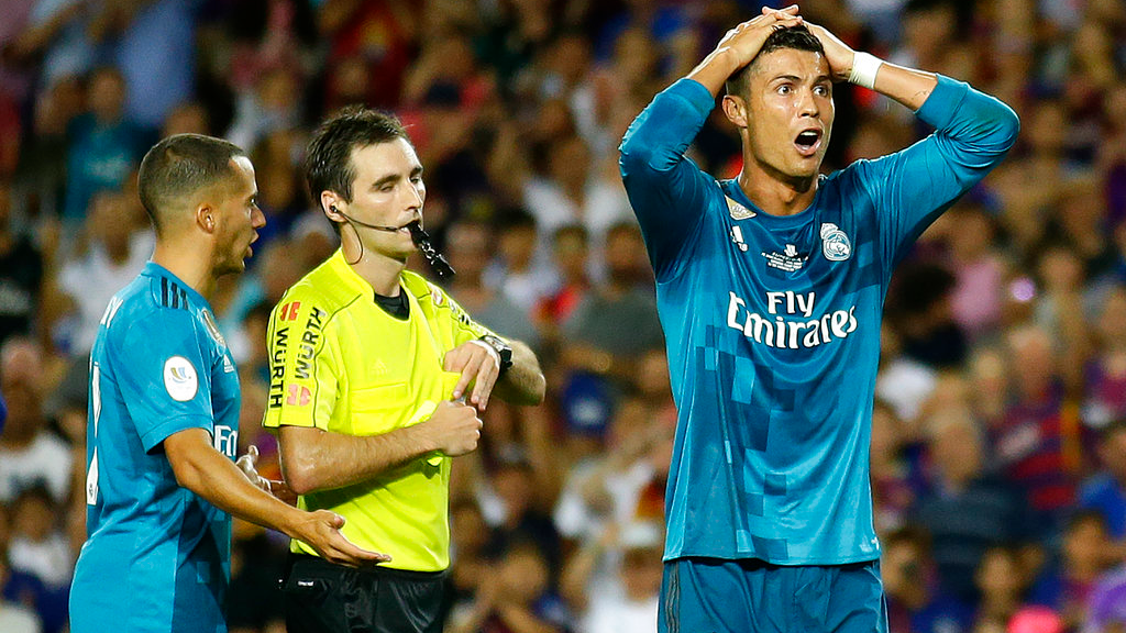 Real Madrid's Cristiano Ronaldo, right, reacts after Referee Ricardo de Burgos shows a yellow card during the Spanish Supercup, first leg, soccer match between FC Barcelona and Real Madrid at the Camp Nou stadium in Barcelona, Spain, Sunday, Aug. 13, 2017. (AP Photo/Manu Fernandez)