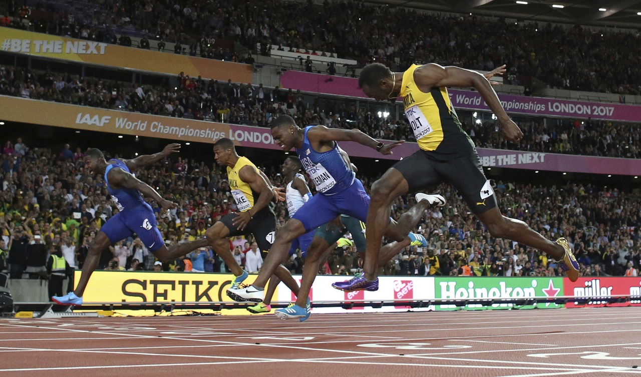 United States' Justin Gatlin, left, and Jamaica's Usain Bolt right, cross the line of the men's 100m final during the World Athletics Championships in London Saturday, Aug. 5, 2017.