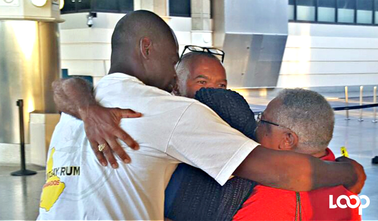John Whitney is embraced by family and friends at Grantley Adams International Airport this afternoon after being evacuated from Tortola.