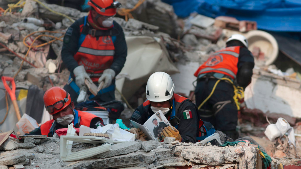 Rescue personnel look through a photo album as they work in rescue operations in the rubble of a building felled by a 7.1 magnitude earthquake, in the Ciudad Jardin neighborhood of Mexico City, Thursday, Sept. 21, 2017. Thousands of professionals and volunteers are working frantically at dozens of wrecked buildings across the capital and nearby states looking for survivors of the powerful quake that hit Tuesday.