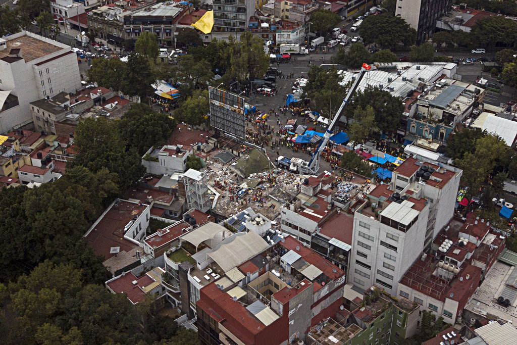Rescue workers race against the clock to reach possible survivors trapped inside the office building on Alvaro Obregon Avenue in the Roma Norte neighborhood of Mexico City, at sunrise on Saturday, Sept. 23, 2017. A strong new earthquake shook Mexico on Saturday morning, causing street signs around the collapsed building to sway and rescue workers to evacuate the site temporarily. (AP Photo/Miguel Tovar)