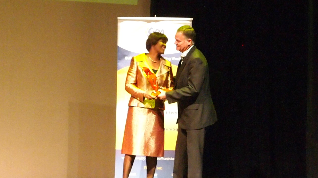 Former Prime Minister of Jamaica, Portia Simpson-Miller receiving an award from the President of the Barbados Small Business Association, Dean Straker.