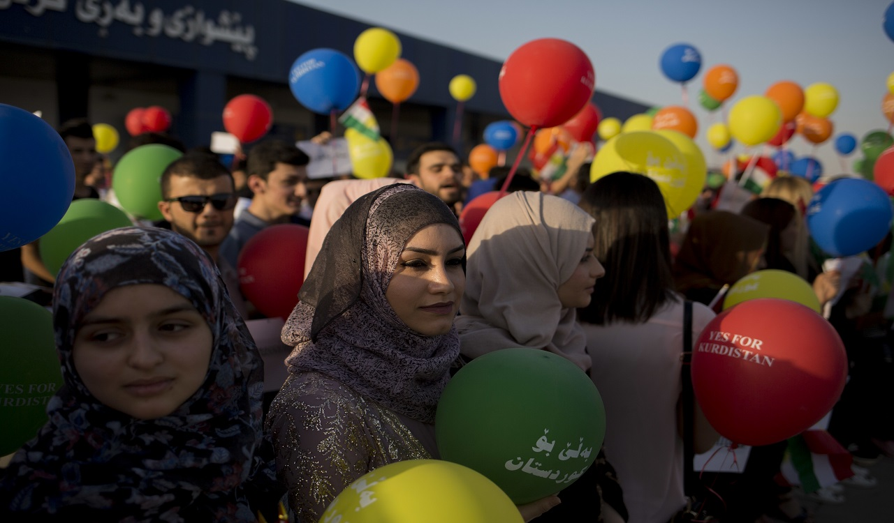Kurdish women hold balloons to protest against the flight ban issued by the Iraq federal government outside the Irbil International Airport in Iraq, Friday, Sept. 29, 2017.