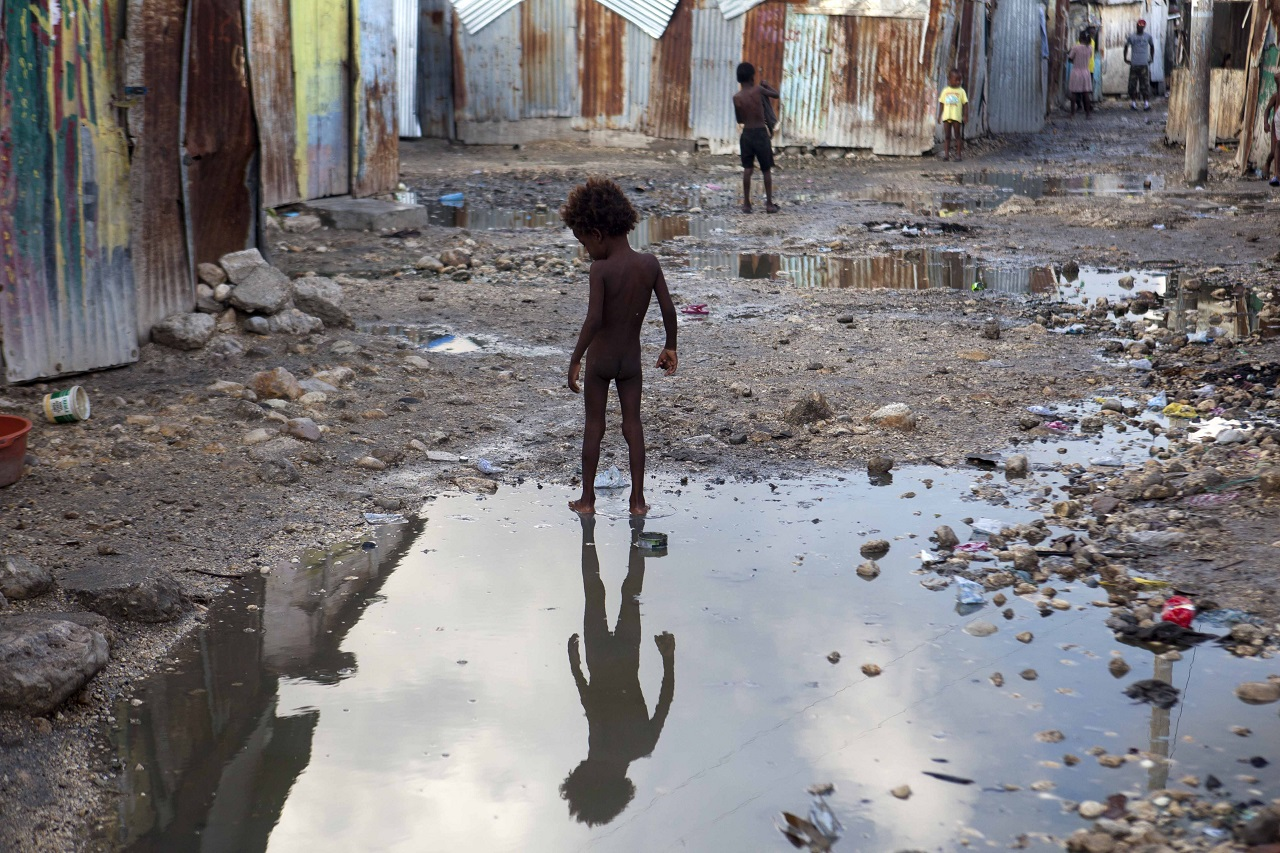 A child plays in a puddle in the seaside slum of Port-au-Prince, Haiti, Wednesday, Sept. 6, 2017. Heavy rain and 185-mph winds lashed the Virgin Islands and Puerto Rico's northeast coast Wednesday as Hurricane Irma roared through Caribbean islands.