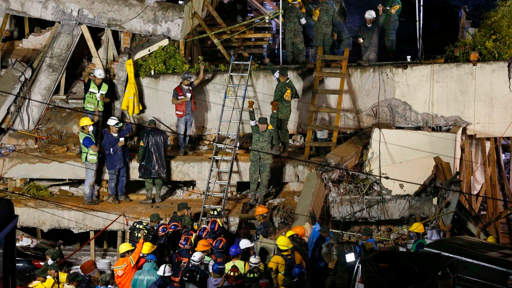 Rescue personnel work on the rescue of a trapped child at the collapsed Enrique Rebsamen primary schoool in Mexico City, Sept. 20, 2017. A wing of the school collapsed after a powerful earthquake jolted central Mexico on Tuesday, killing scores of children and trapping others.