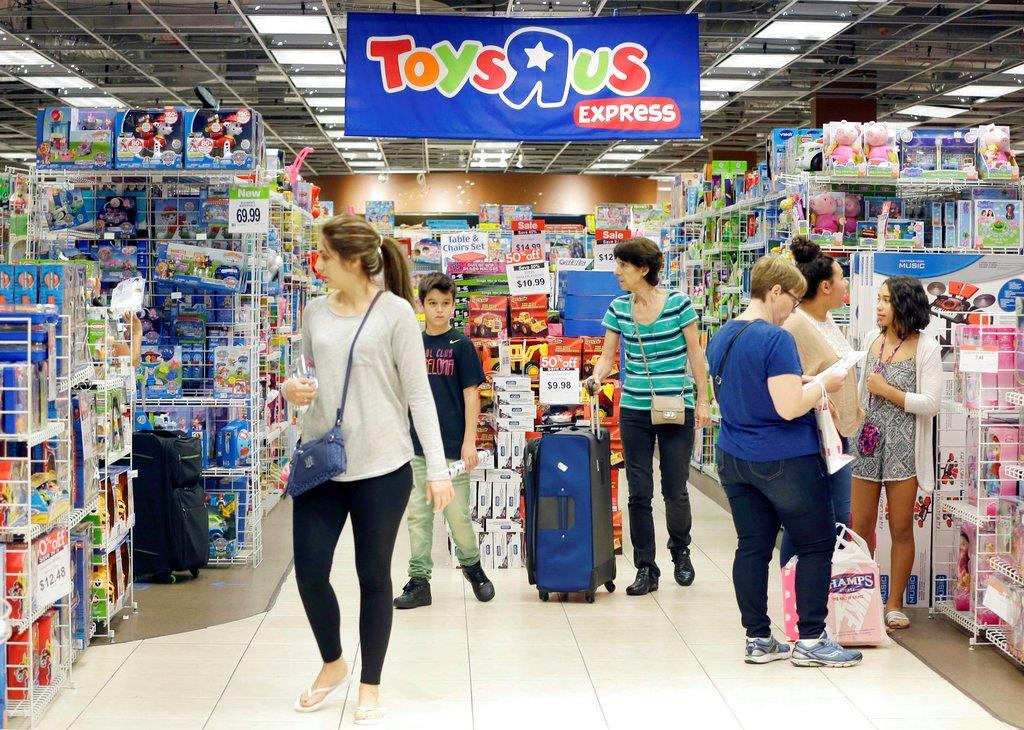 In this Friday, Nov. 25, 2016, file photo, shoppers shop in a Toys R Us store on Black Friday in Miami. Toys R Us, the pioneering big box toy retailer, announced late Monday, Sept. 18, 2017 it has filed for Chapter 11 bankruptcy protection while continuing with normal business operations. (AP Photo/Alan Diaz, File)