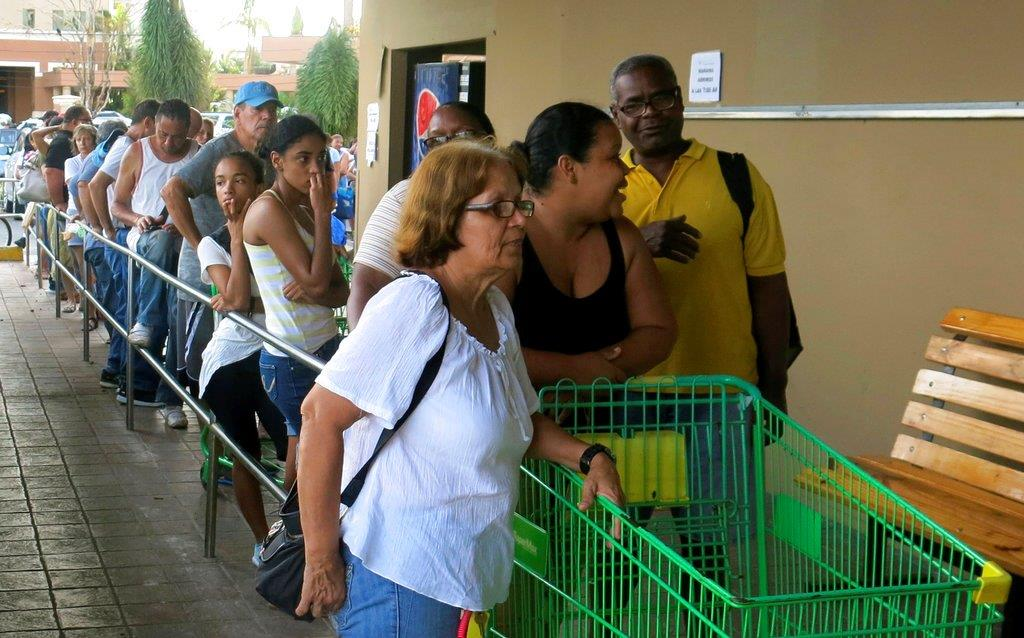 People wait in line outside a grocery store to buy food that wouldn't spoil and that they could prepare without electricity, in San Juan, Monday, Sept. 25, 2017. Most stores and restaurants remained closed Monday. Nearly all of Puerto Rico was without power or water five days after Hurricane Maria.(AP Photo/Ben Fox)