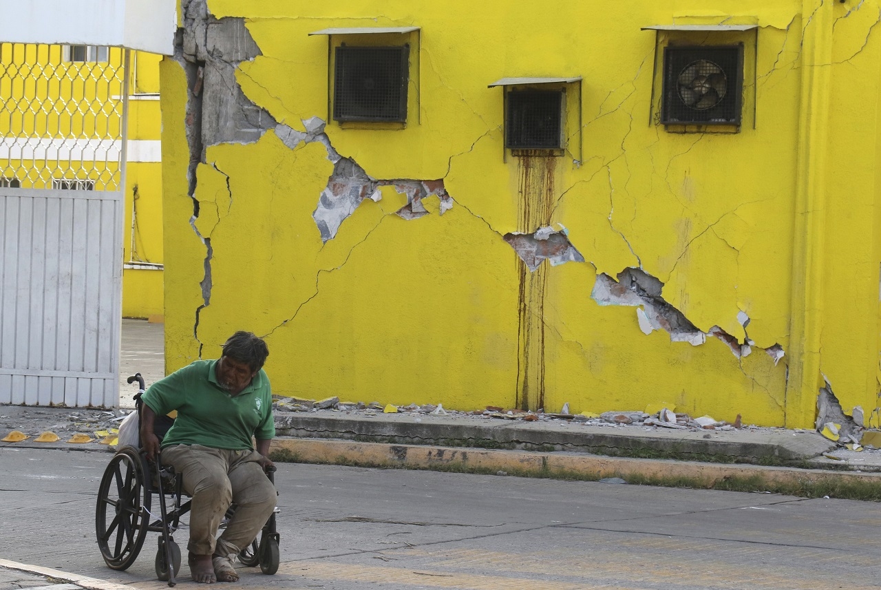 A man sits in his wheelchair backdropped by a building damaged in a massive earthquake, in Juchitan, Oaxaca state, Mexico Friday, Sept. 8, 2017.