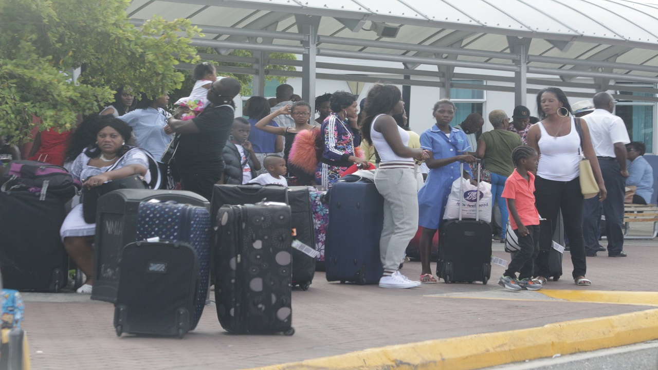 People gather outside the Norman Manley International Airport in Kingston after arriving on a flight. (PHOTO: File)