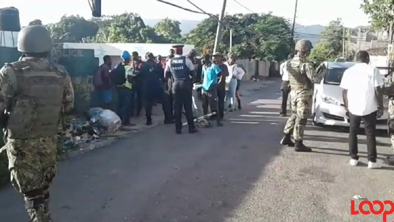 Members of the security forces interact with residents of Mount Salem in St James on the first day of the special operation in the community.
